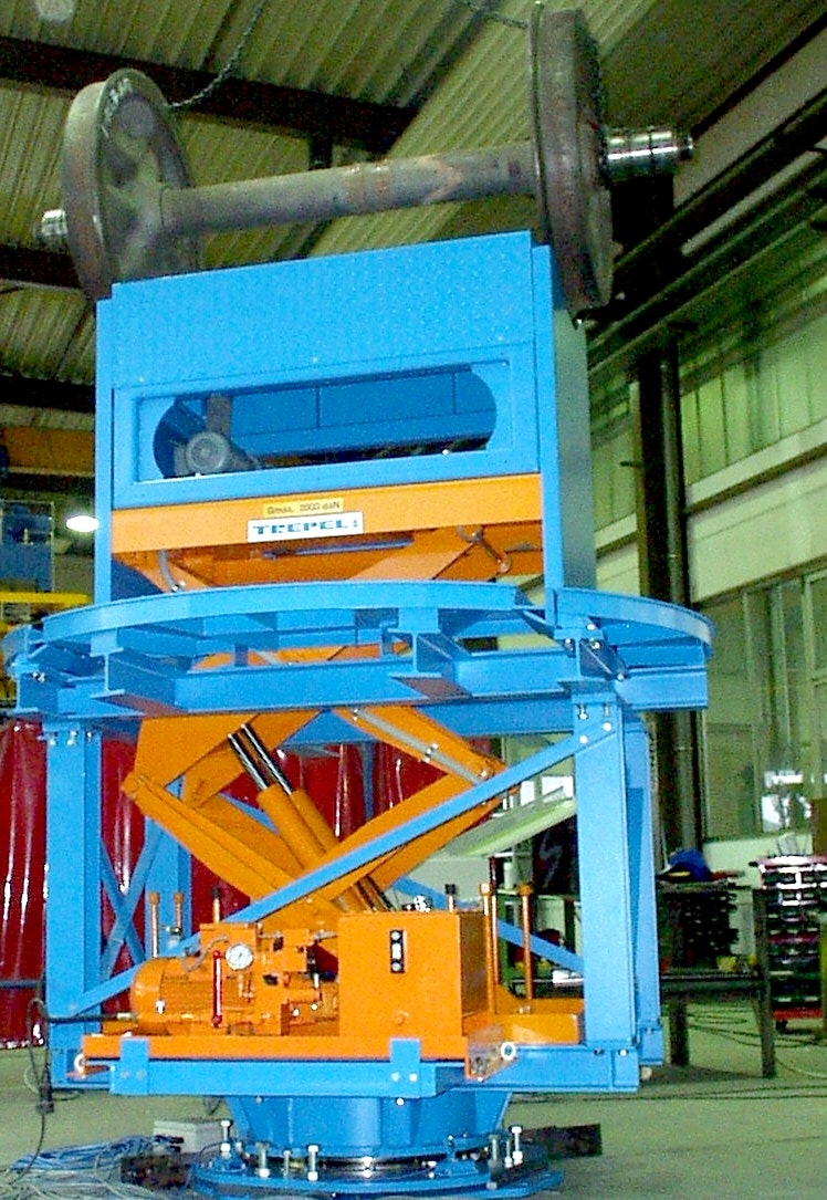 This customer-specific device is used for lifting, rolling and turning wheelsets with and without attachments with fixed track width. Lifting and turning device with wheelset during preliminary acceptance test in the lifted condition. This device will be embedded in a pit on site.