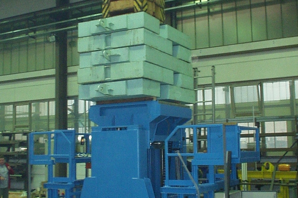 The wheelset drop (wheel changing device) is used to lift and lower rail vehicle cars for changing the bolster springs from bogies and for transporting rail vehicle parts (max. 25 t) as well as for transporting the dismantled wheelsets. The picture shows loading/ stress test with a stack of concrete slabs during the factory acceptance test.