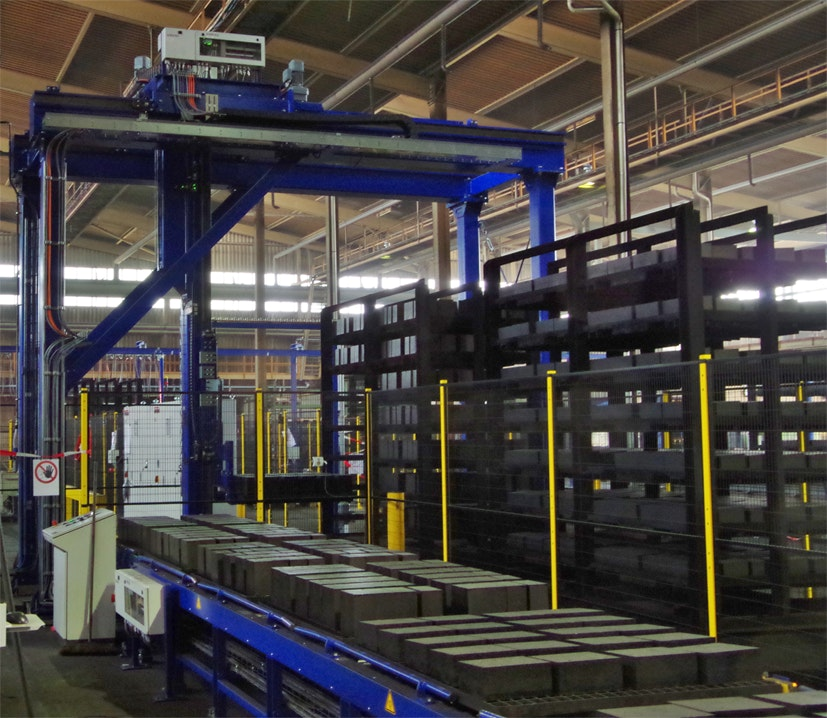 Gantry for automated unloading loads on pallets from trolleys: the loaded pallets with refractory bricks are placed onto a roller conveyor which transports the refractory bricks to a packaging line.
