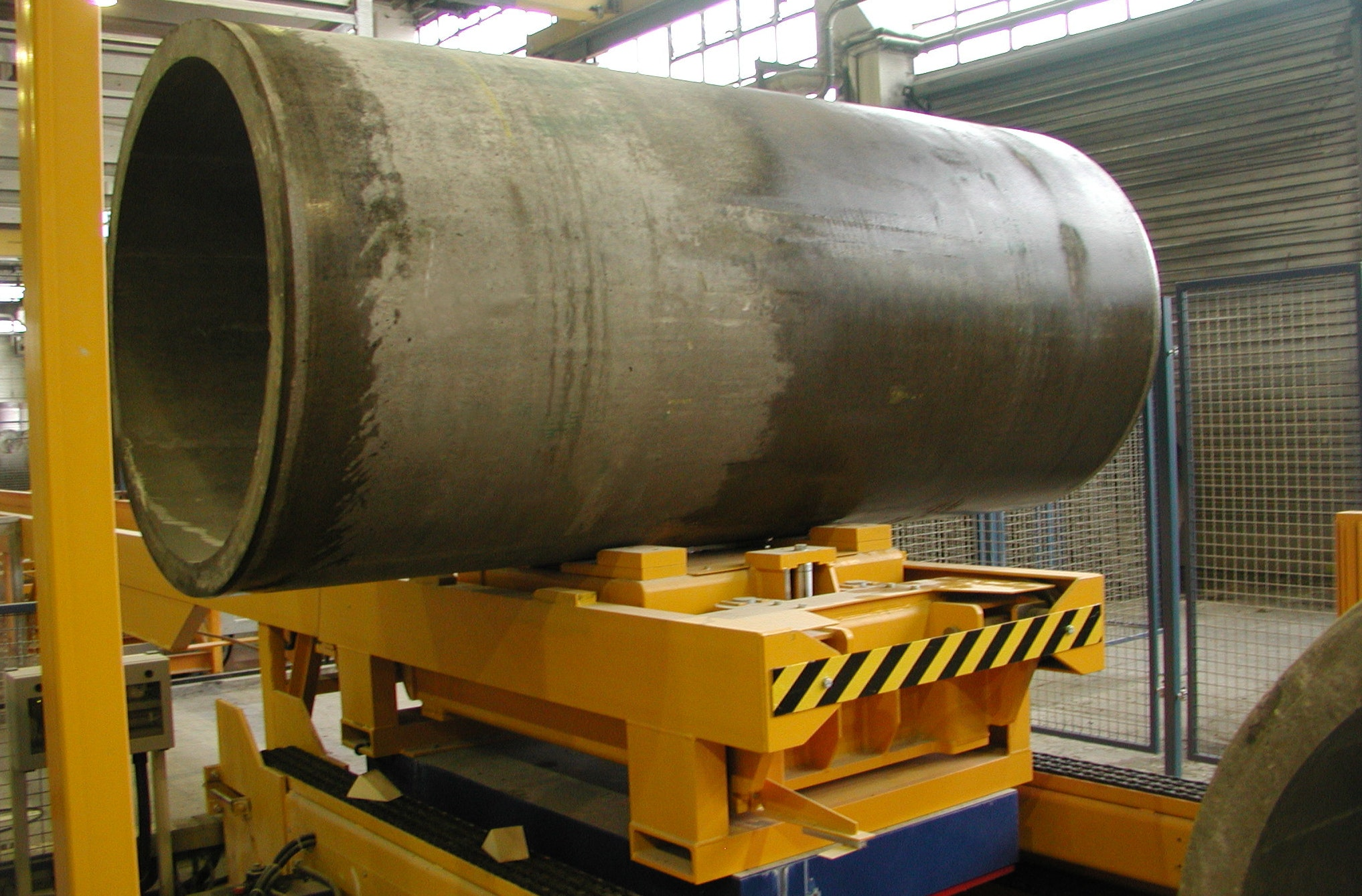 Transport car with horizontally arranged concrete pipes: This transport car, which is equipped with a lifting table, transports the pipes on a fixed transport section to the final processing.