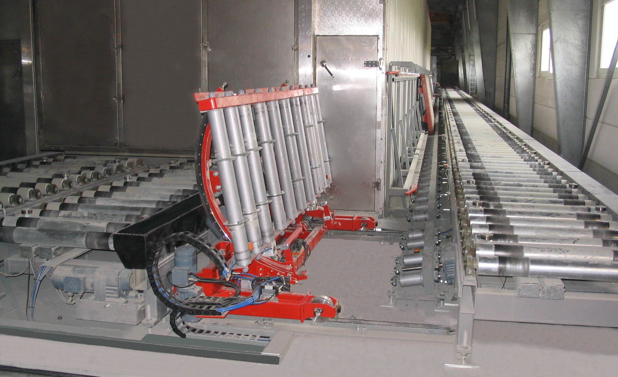 Tilting car for transport frames:   The tilting car (with roller conveyor) is a special construction that allows the transport frame to be turned by approx. 80° and then transferred to a vertical support roller conveyor (inclination approx. 80°). On the picture there is the empty tilting car (turmed by approx. 80°). On the right,  next to the roller conveyor, the vertical support roller conveyor can be seen on the wall (inclination approx. 80°)..