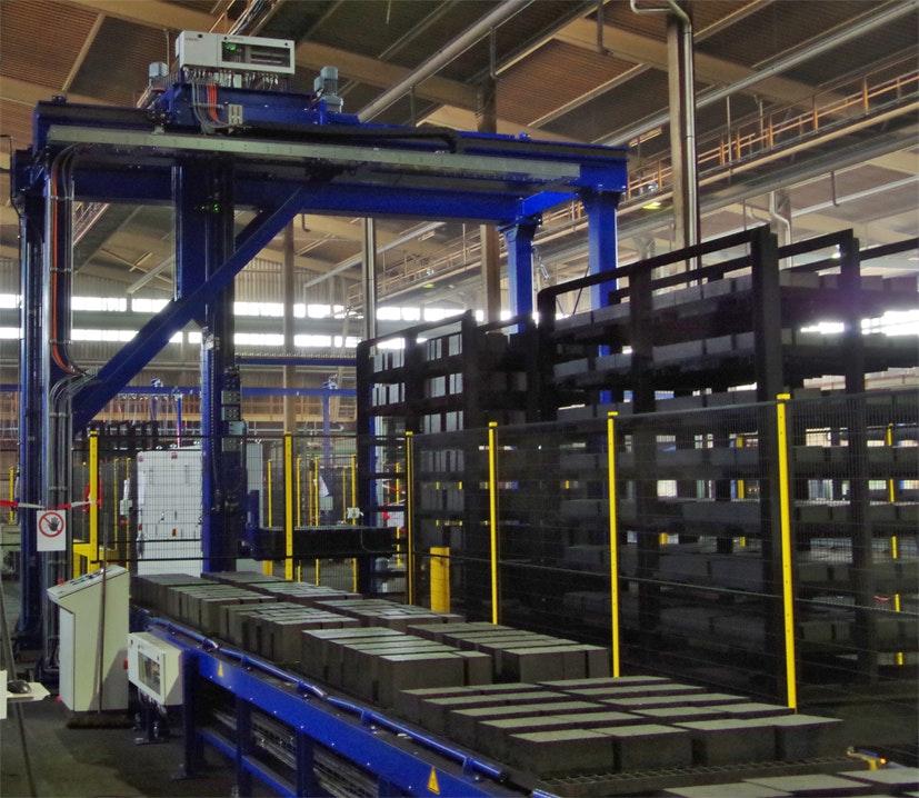 Portal zur automatisierten palettenweisen Entladung von Hordenwagen: DasPortal setzt die entnommenen Paletten mit Feuerfeststeinen auf einer Rollenbahn ab, die die Steine dann der Verpackungslinie zuführt.