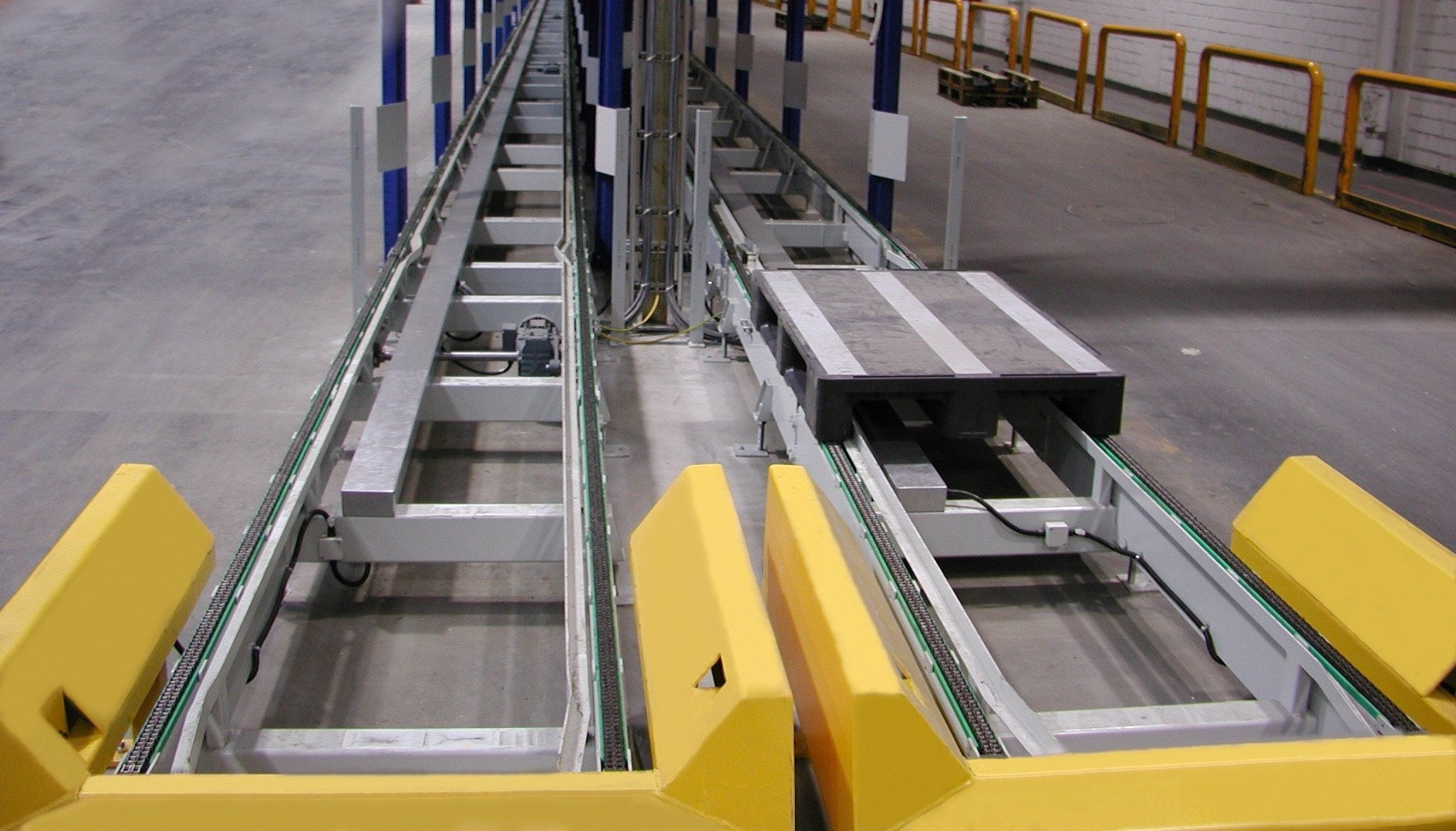 Chain conveyor with support tool by loading and unloading für specific pallets